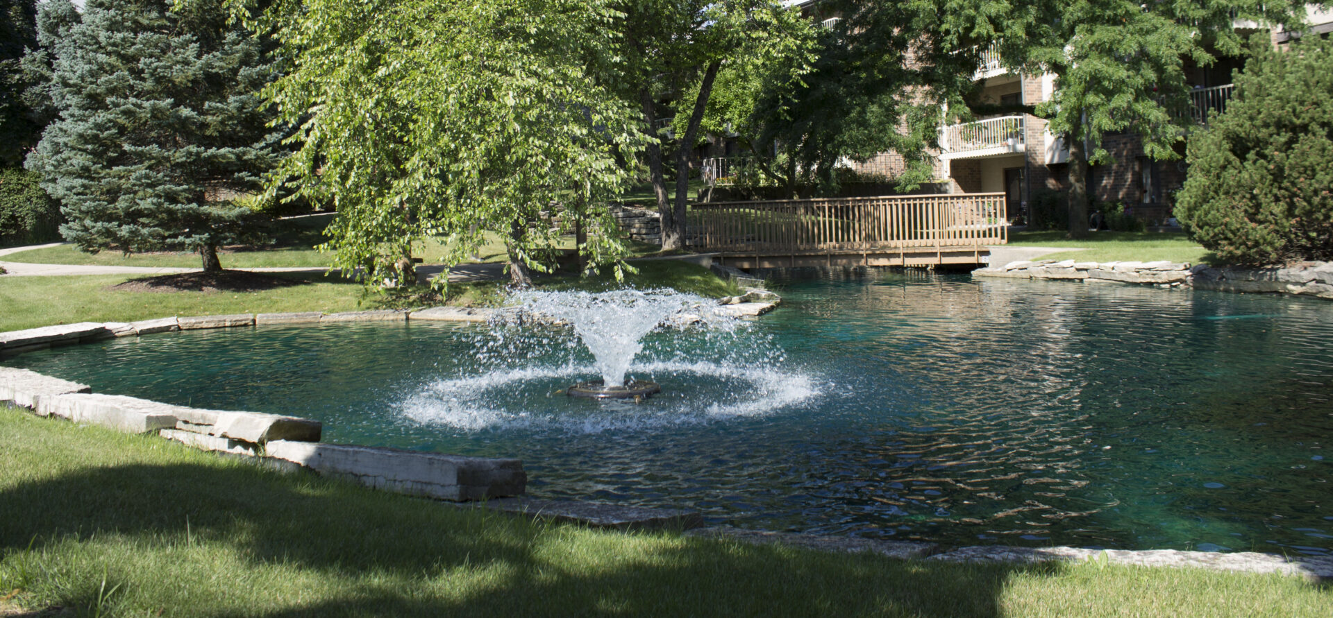 A fountain in a pond outside the independent living apartments at vmp milwaukee.