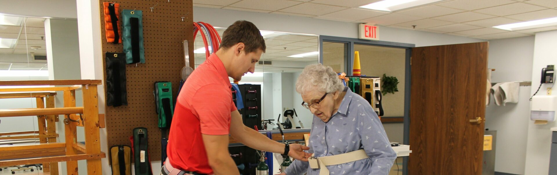 A physical therapist helping an elderly lady walk.
