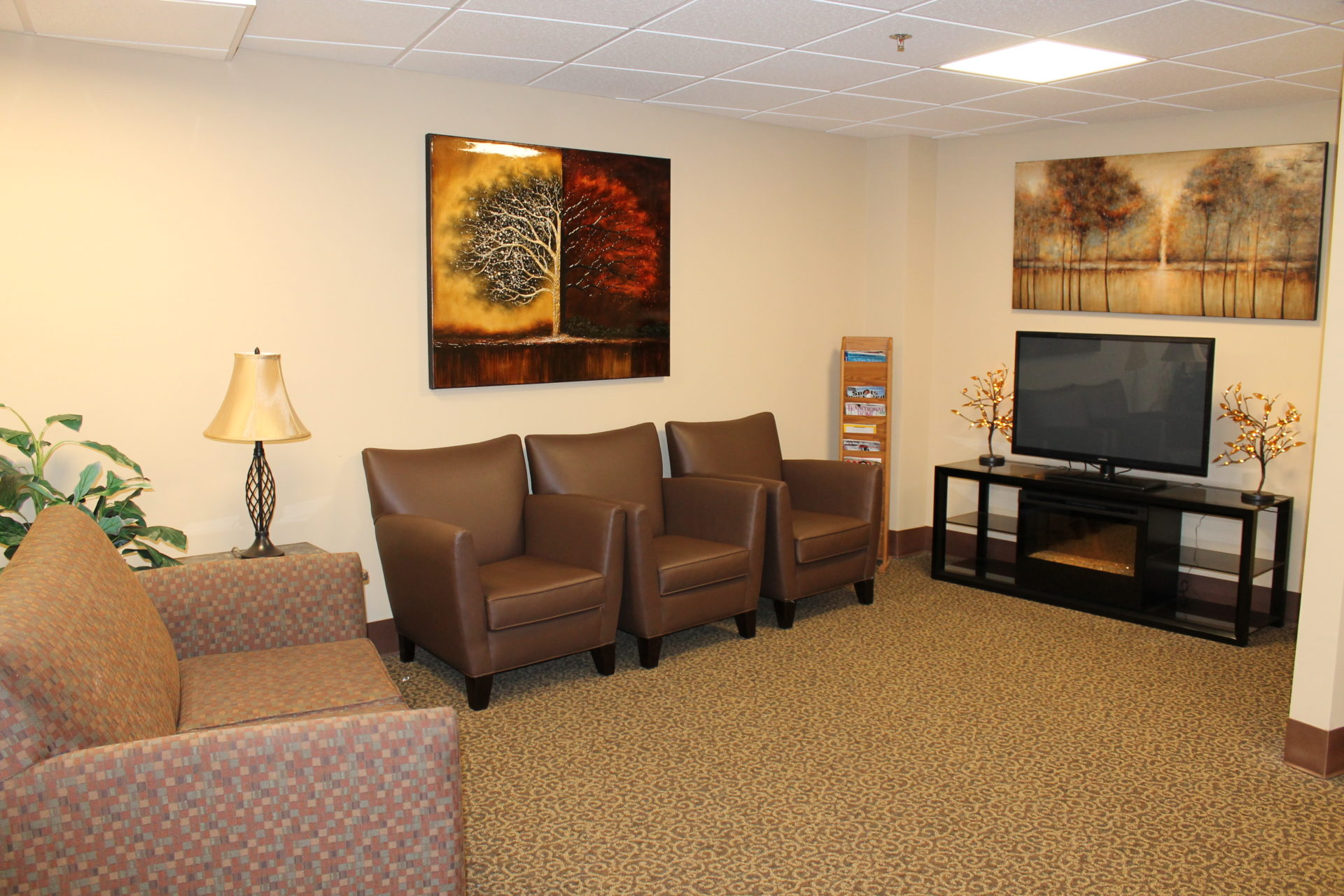 A couch and a chair in front of a TV at VMP Milwaukee's skilled nursing facility.